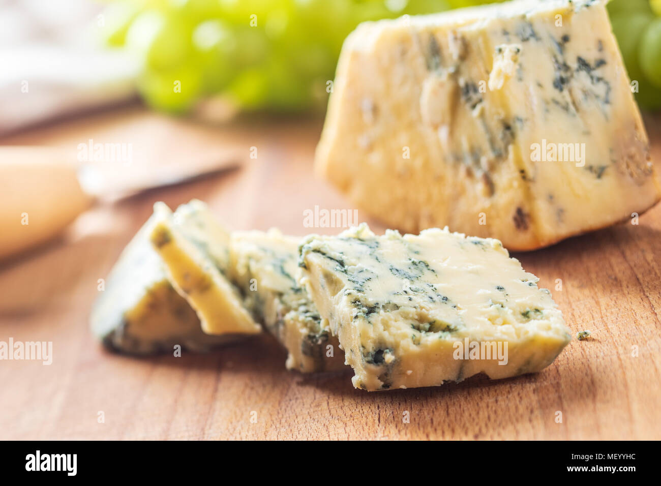 Tasty blue cheese on old kitchen table. - Stock Image