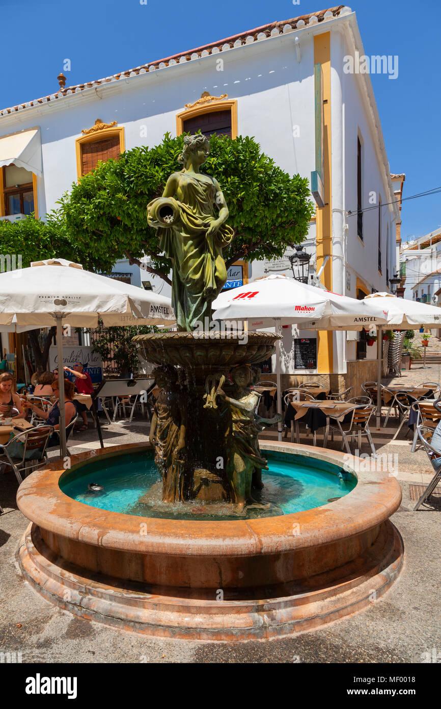 Estepona, Malaga, Spain: A colourful street scene - a water fountain - Stock Image