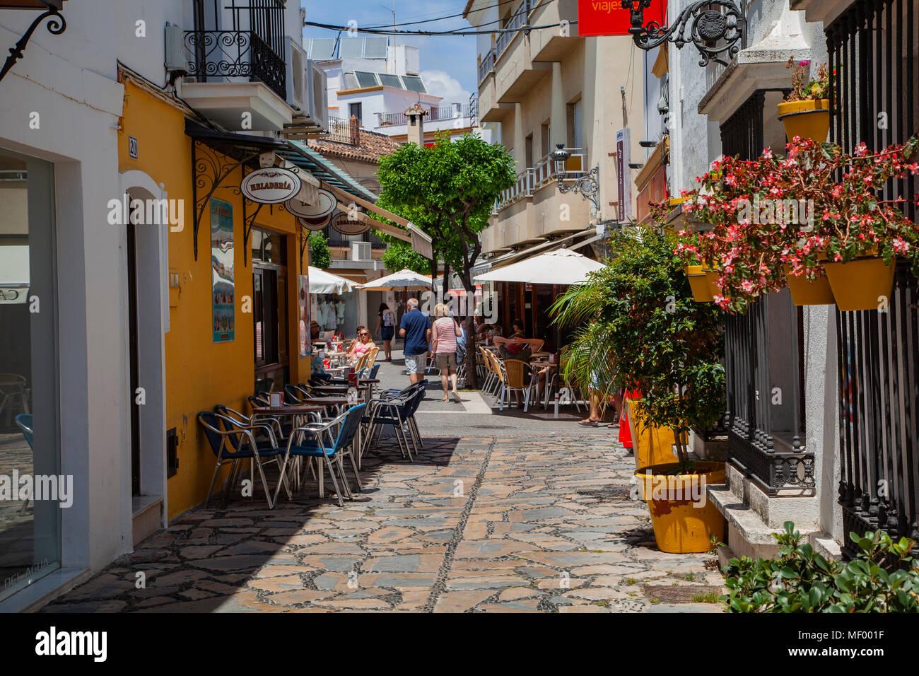 Estepona, Malaga, Spain: A colourful street scene: tourists browse the local restaurants - Stock Image