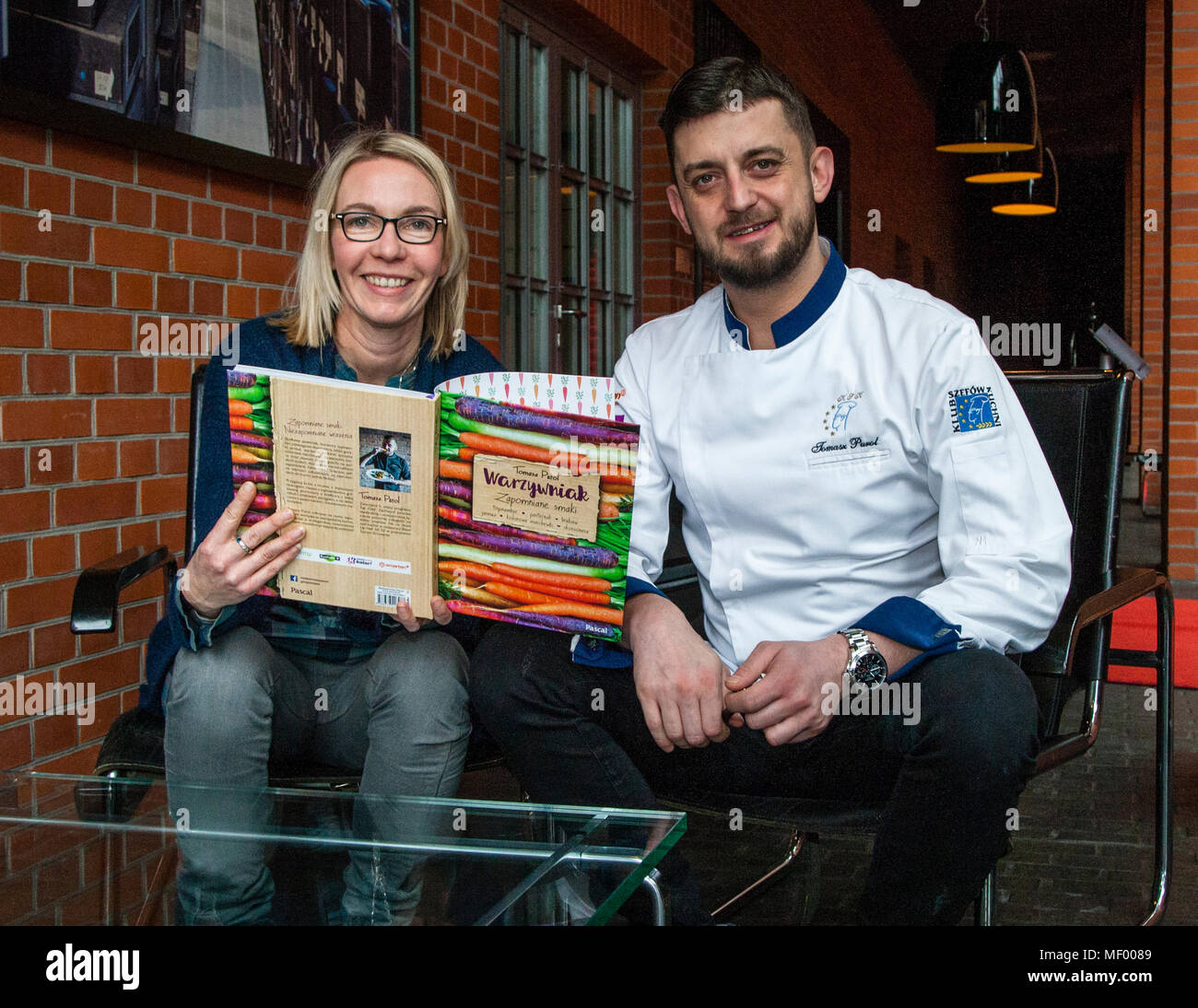 Tomasz Purol explains the structure of his cookbook to journalist Angela Berg. Chef Tomasz Purol in Hotel Blow up 5050, Posen Stock Photo
