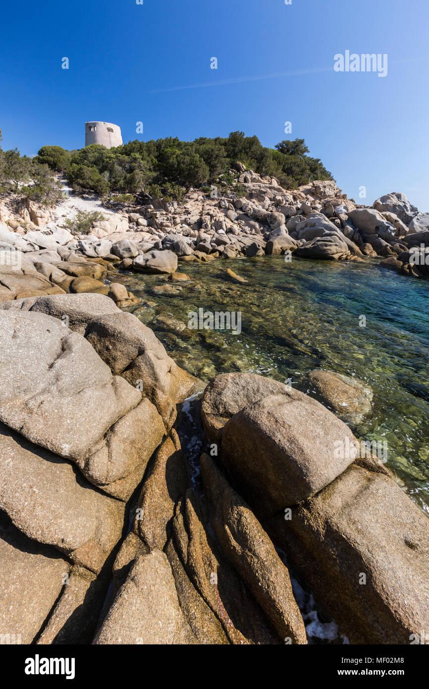 Cliffs and rocks frame the tower overlooking the turquoise sea Cala Pira Castiadas Cagliari Sardinia Italy Europe - Stock Image