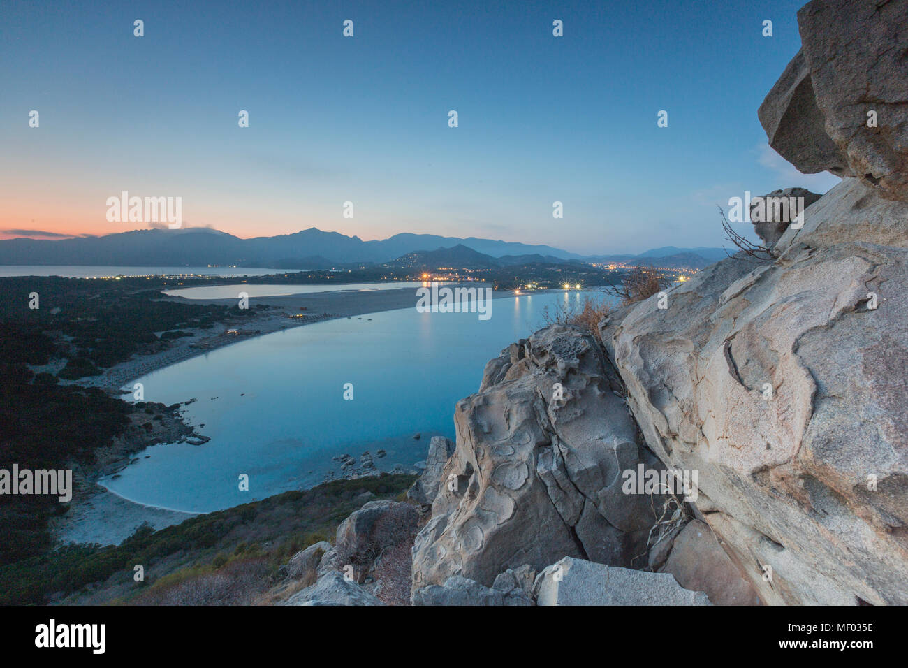 Top view of the bay with sandy beaches and lights of a village at dusk Porto Giunco Villasimius Cagliari Sardinia Italy Europe - Stock Image