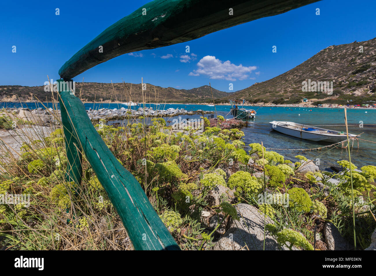 Mediterranean plants frame the fishing boats in the turquoise sea Punta Molentis Villasimius Cagliari Sardinia Italy Europe - Stock Image