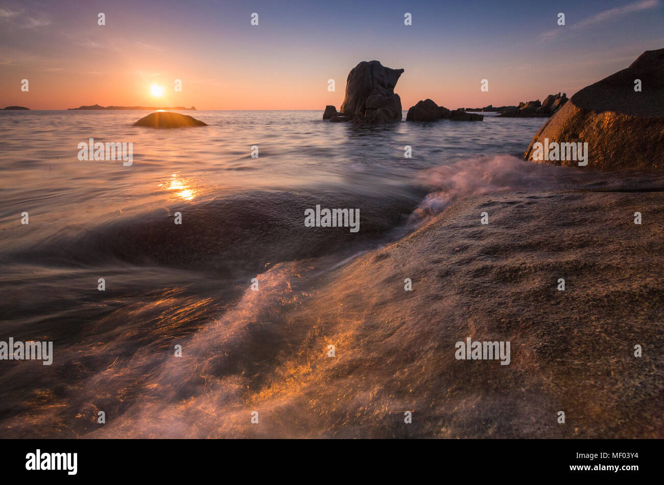 Waves crashing on cliffs under the fiery sky at sunrise Punta Molentis Villasimius Cagliari Sardinia Italy Europe - Stock Image
