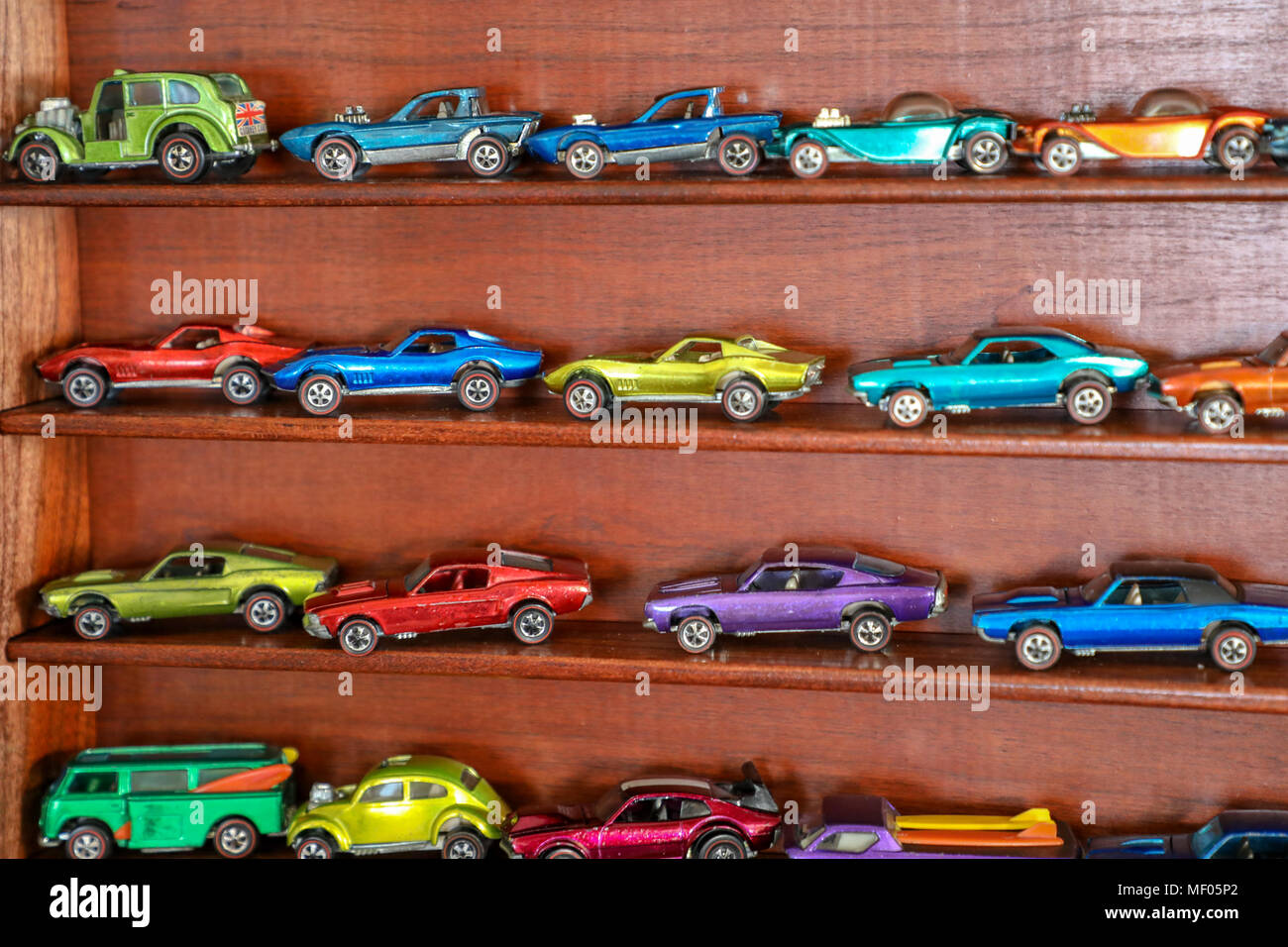 Multi colored Redline Hot Wheels in a cherry display case. - Stock Image
