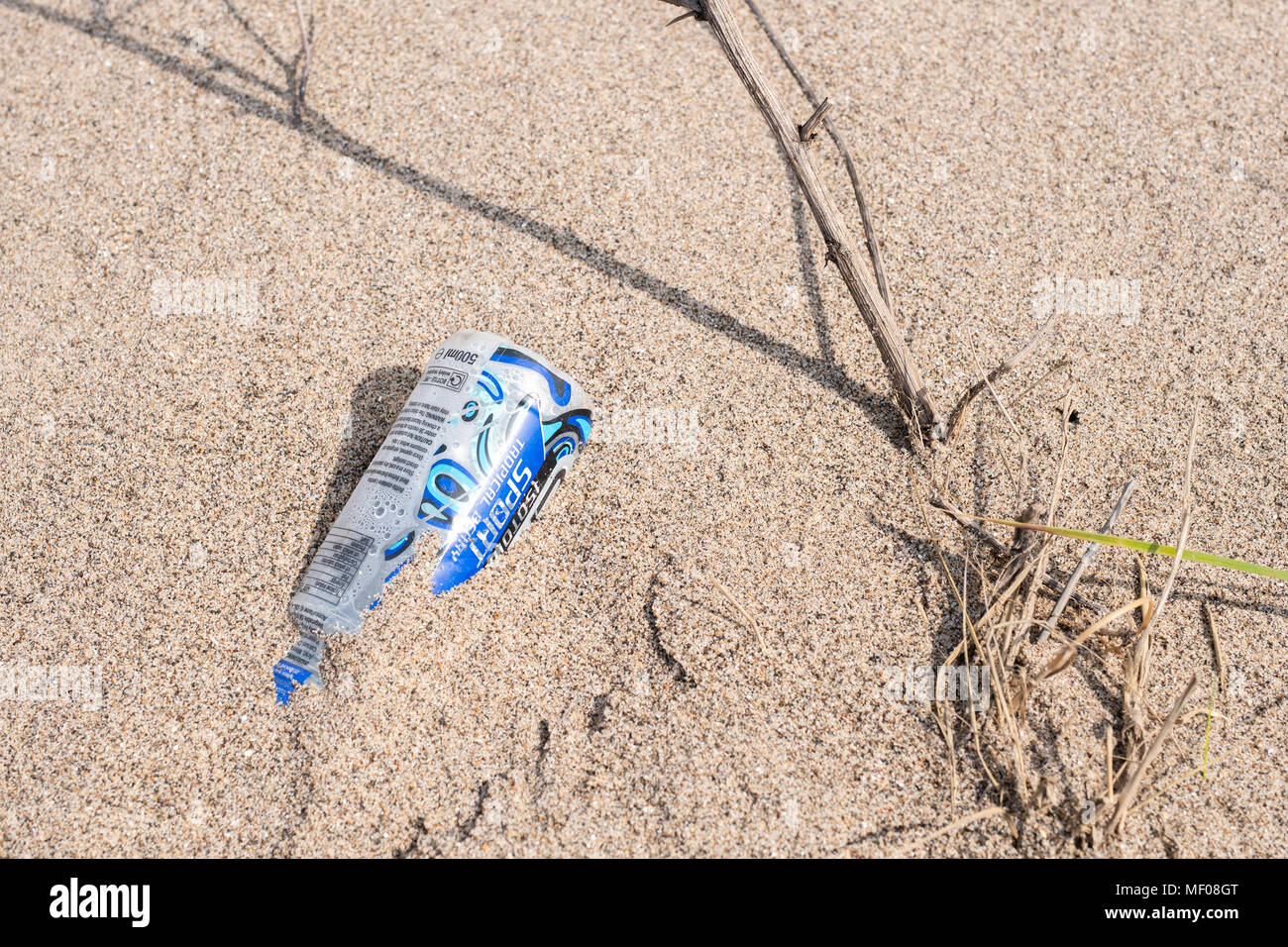 Drinks bottle discarded on beach - Stock Image