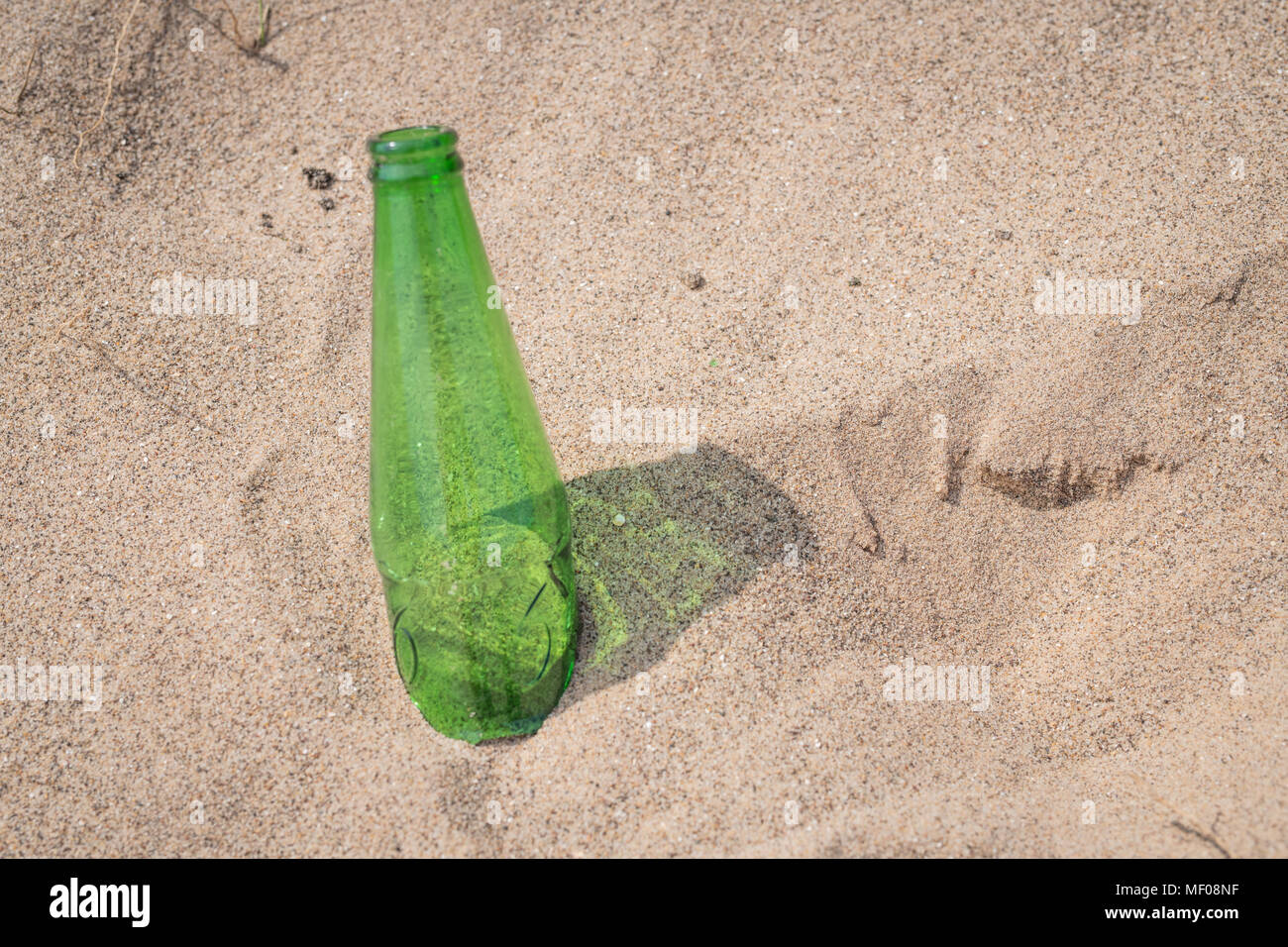 Green bottle discarded on beach - Stock Image