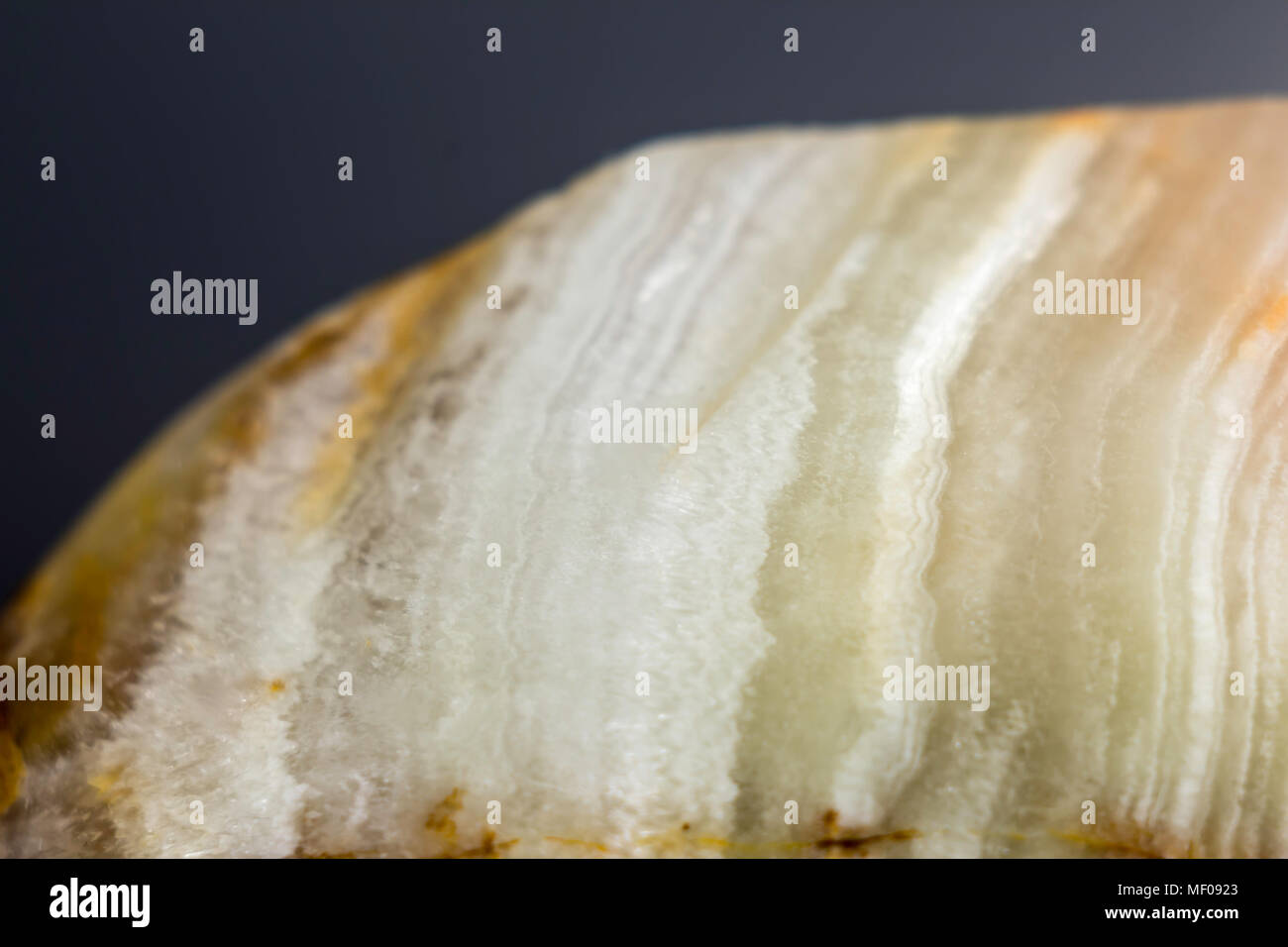 Macro photo texture of polished onyx stone on a gray background. Photo for the site about geology, stones, jewelry, handwork, textures,art, astronomy. - Stock Image