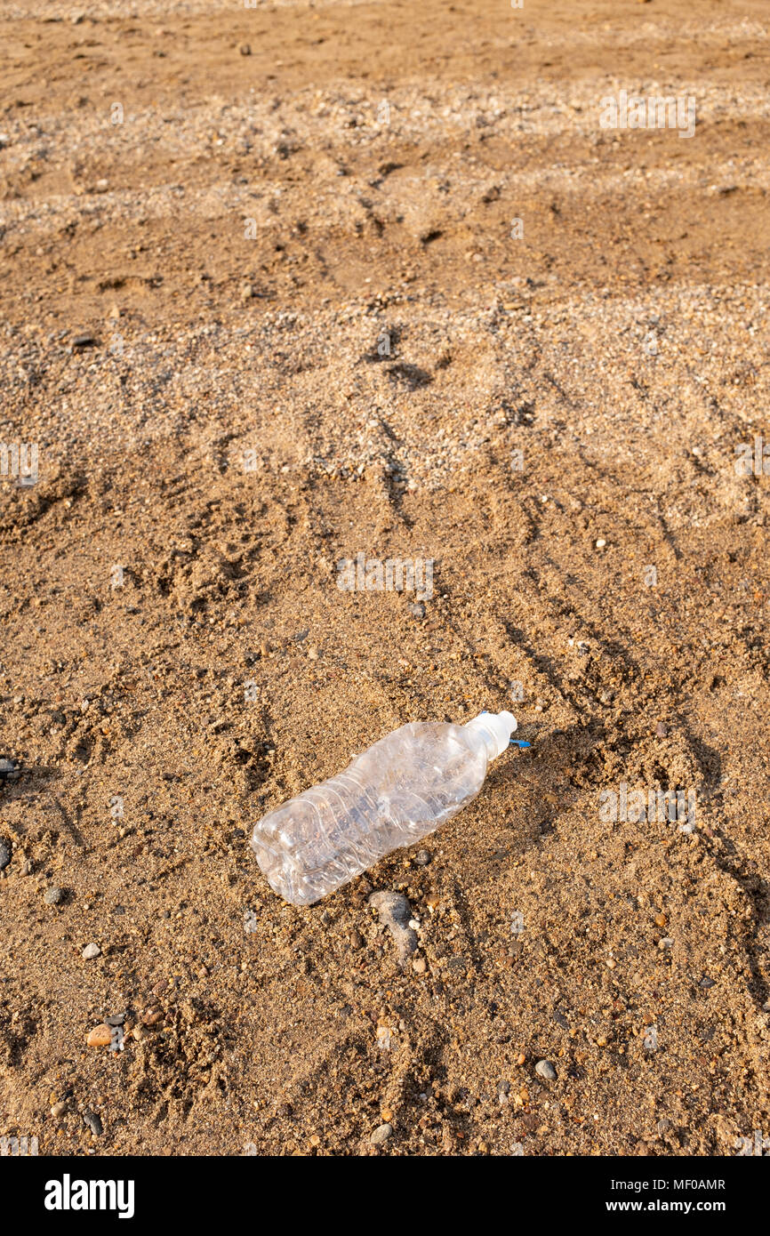 Plastic bottle discarded on a British beach. - Stock Image