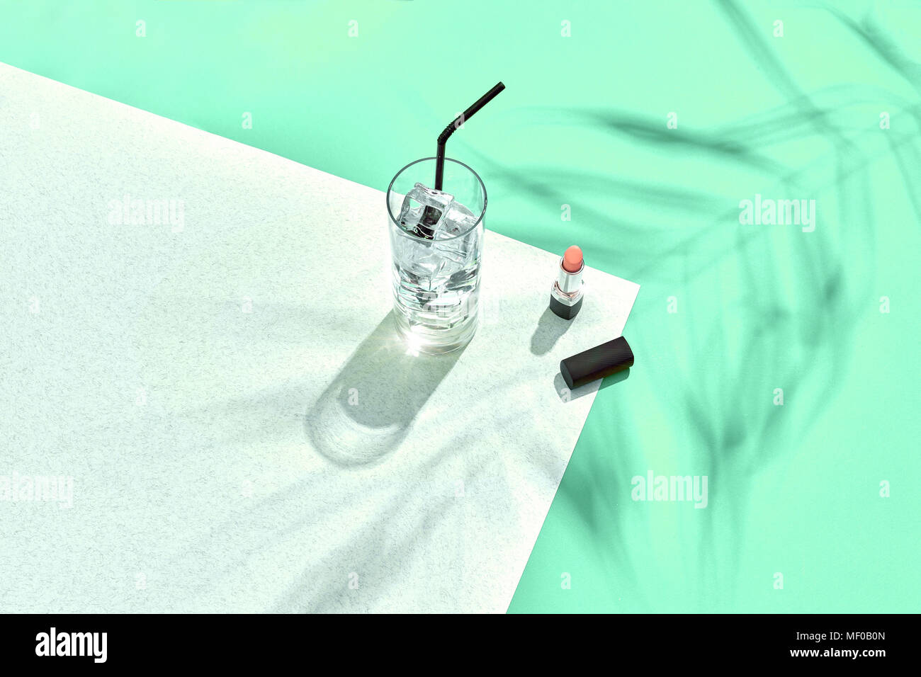 High angle view of lipstick and drinking glass with ice on table. Blue and white background with shadow from a palm leaf - Stock Image