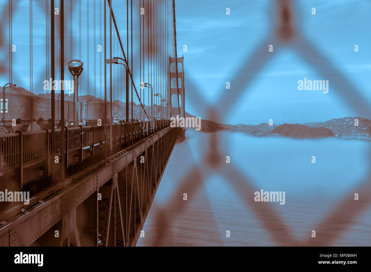 View of the Golden Gate Bridge, with the fog underneath, through the safety fence, San Francisco, California, United States. - Stock Image