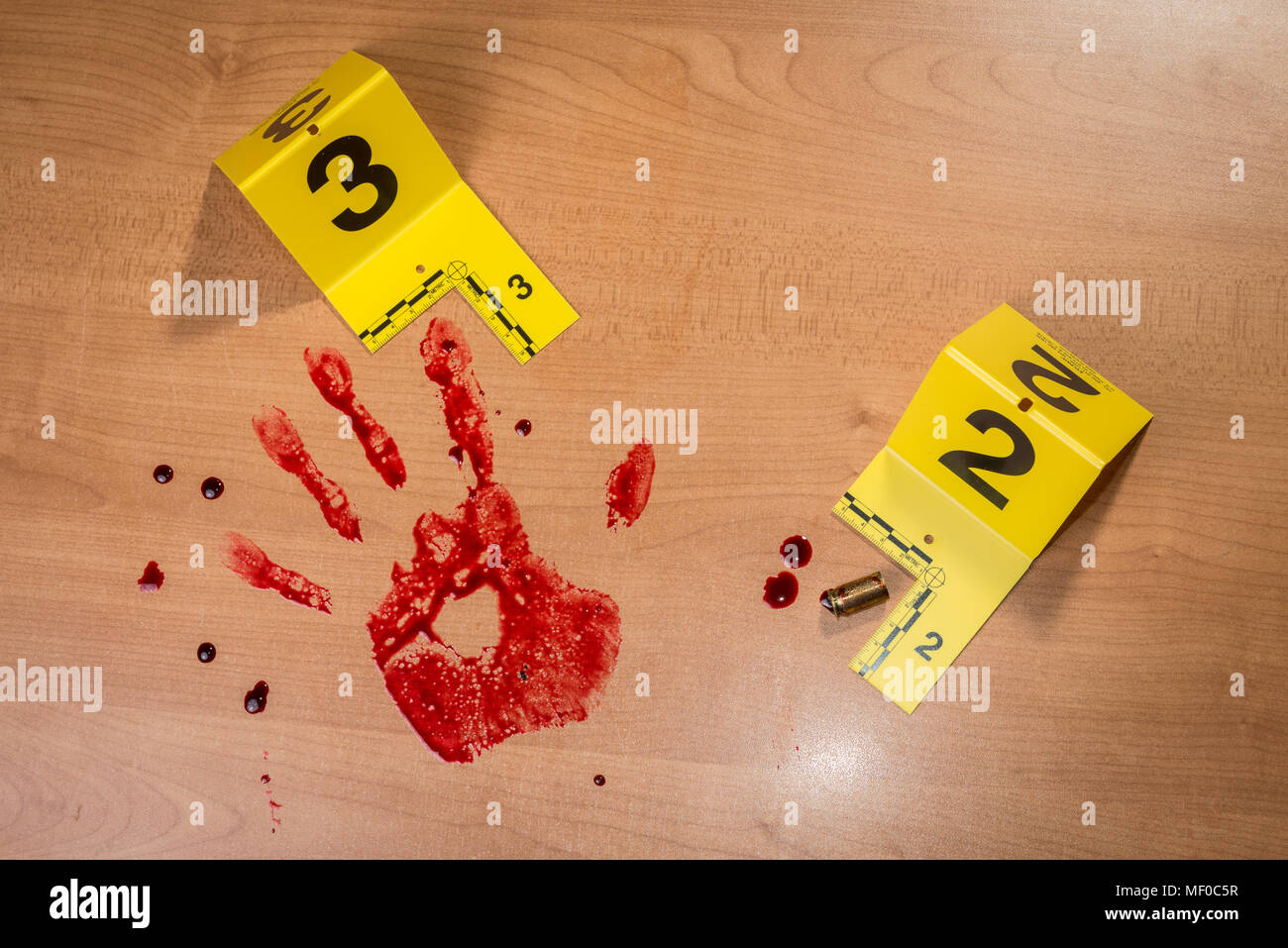 A bloody handprint beside an expended shell casing, both marked with crime scene evidence markers. - Stock Image