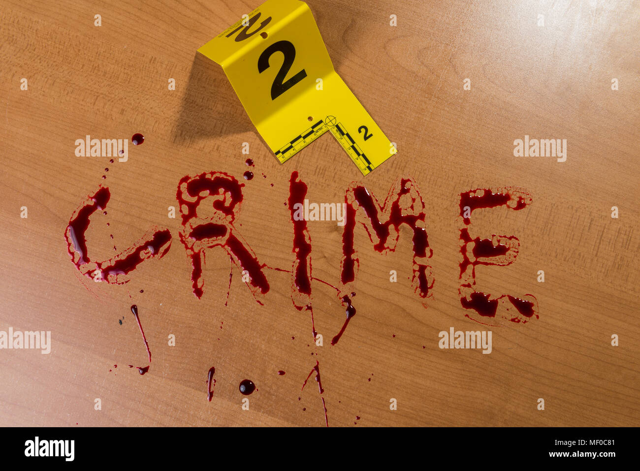 """The word """"crime"""" written in blood on a wood surface beside a bloody knife, both marked by crime scene evidence markers. - Stock Image"""