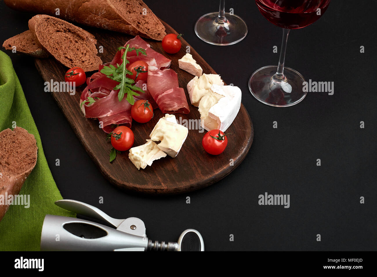 Cheese, prosciutto, bread, vegetables and spices on wooden board on black background with copy space - Stock Image