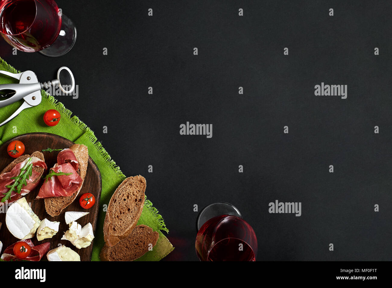 Prosciutto, salami, baguette slices, tomatoes and nutson rustic wooden board, two glasses of red wine over black background - Stock Image