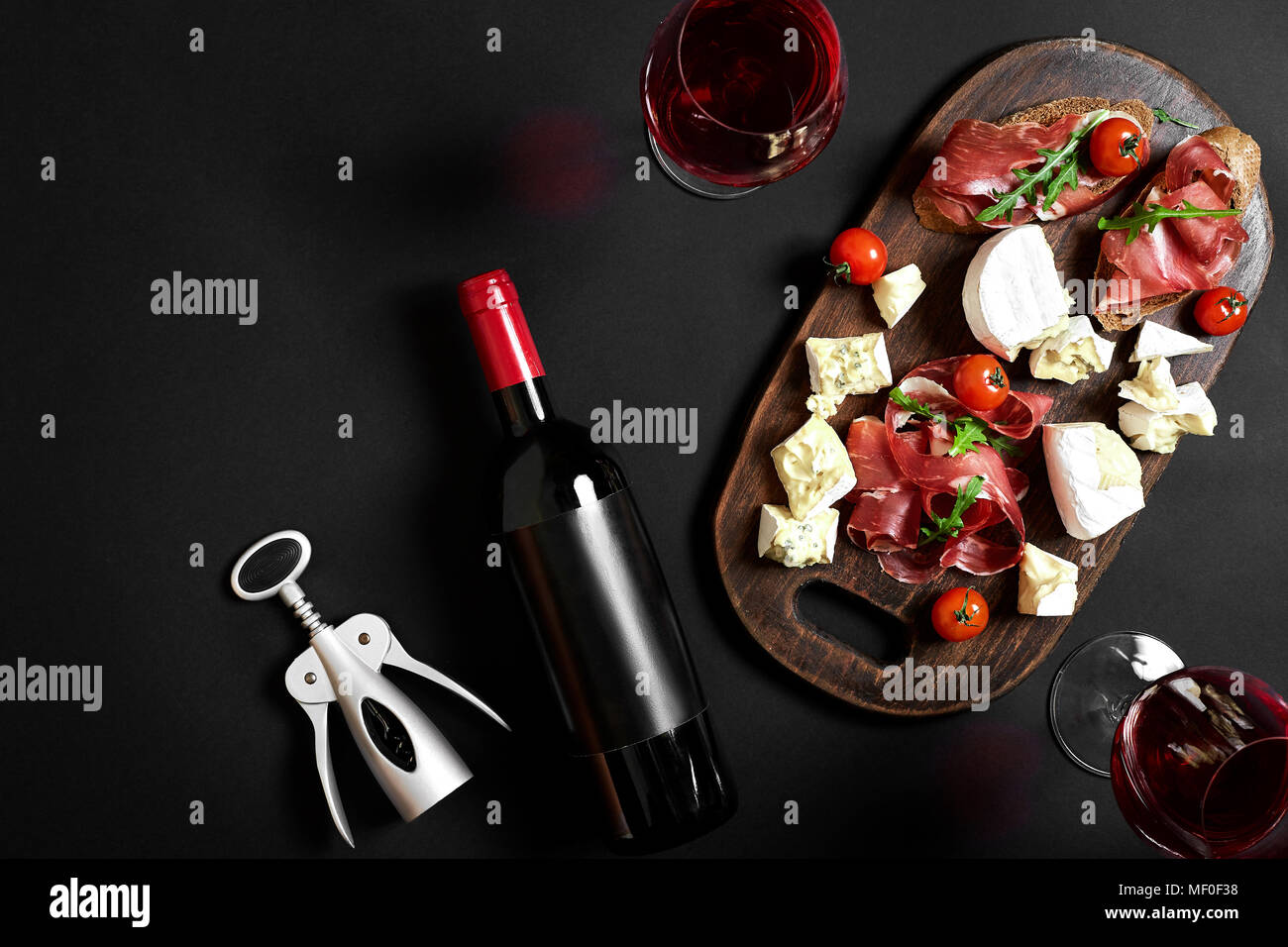 Delicious appetizer to wine - ham, cheese, baguette slices, tomatoes, served on a wooden board, and glass with red wine on black surface - Stock Image