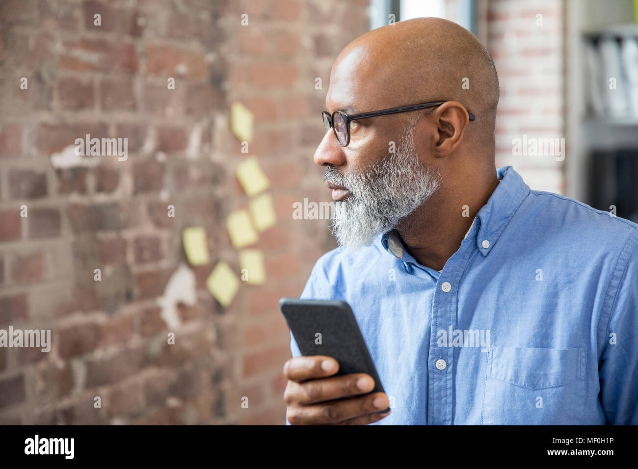 Businessman with cell phone in a loft - Stock Image