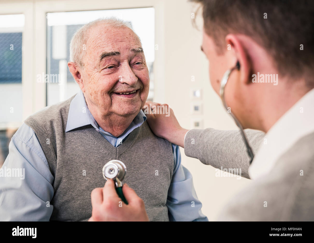 Senior man smiling at nurse with stethoscope at home - Stock Image