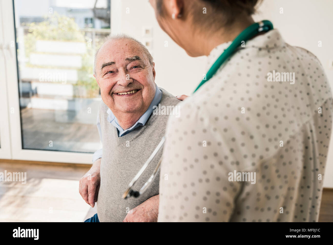 Senior man smiling at nurse at home - Stock Image