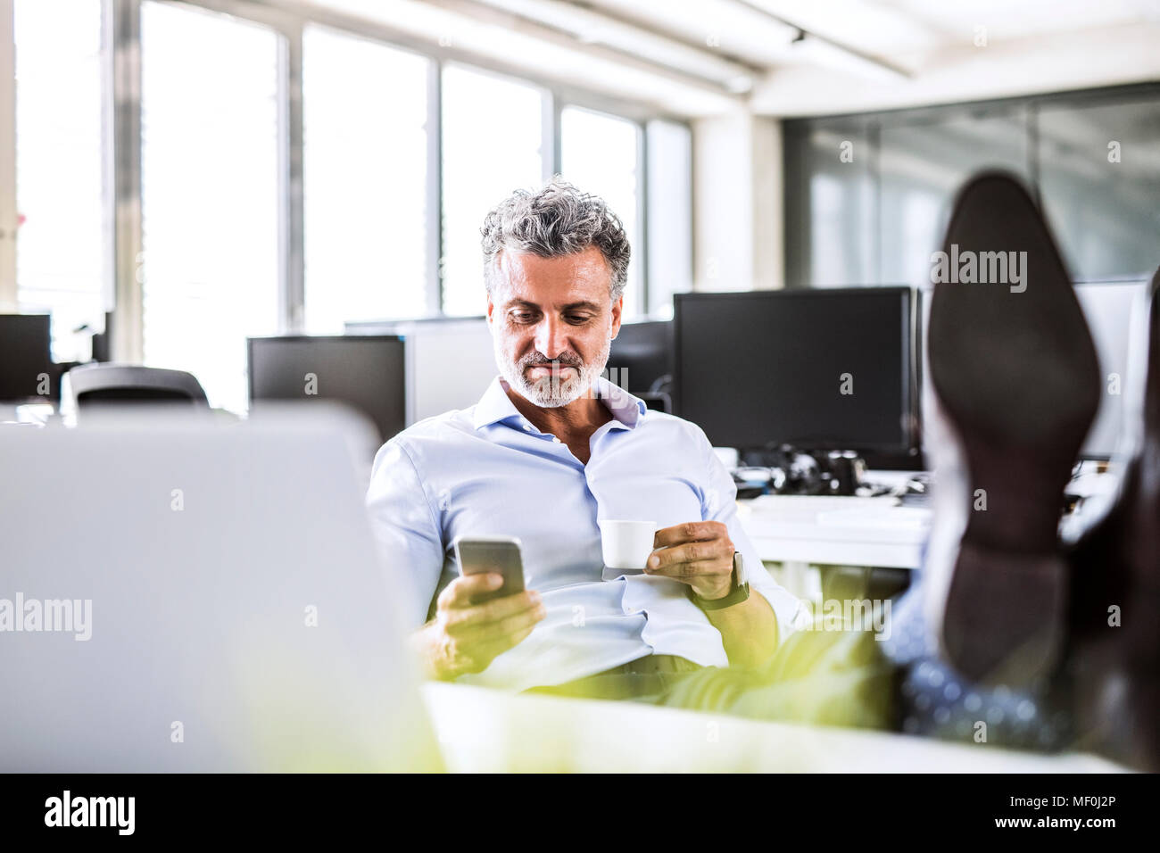 Relaxed mature businessman sitting at desk in office using cell phone and drinking coffee - Stock Image