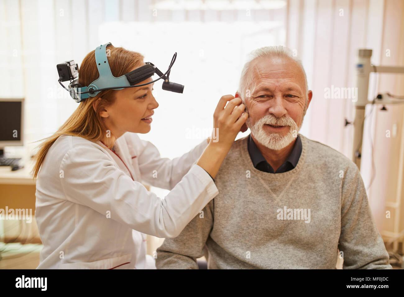 ENT physician examining ear of a senior man Stock Photo