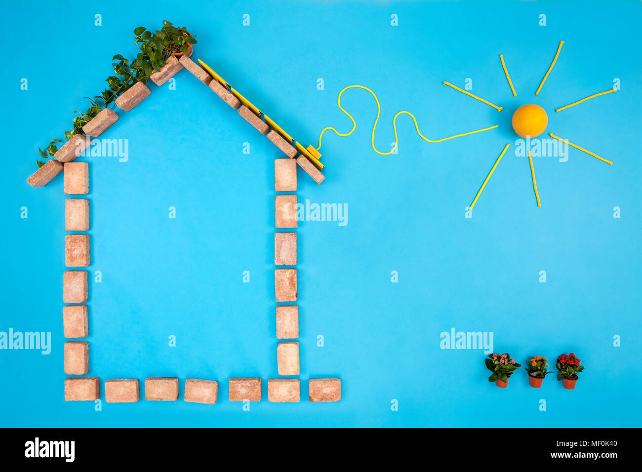 House shape made of bricks on blue background, with solar panels plugged to sun - Stock Image