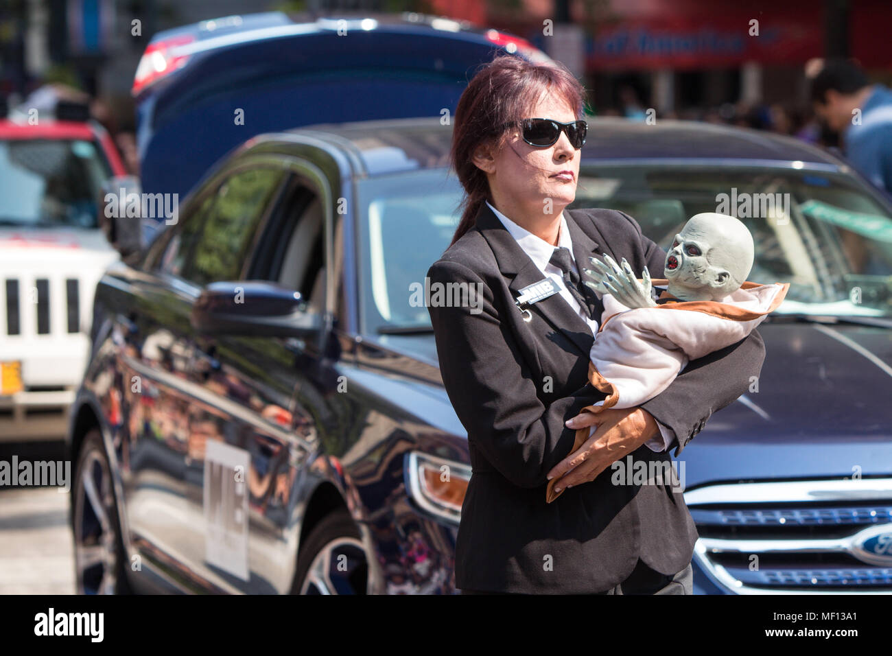 A woman dressed like a Men In Black agent carries an alien baby while walking in the annual Dragon Con Parade on September 5, 2015 in Atlanta, GA. - Stock Image