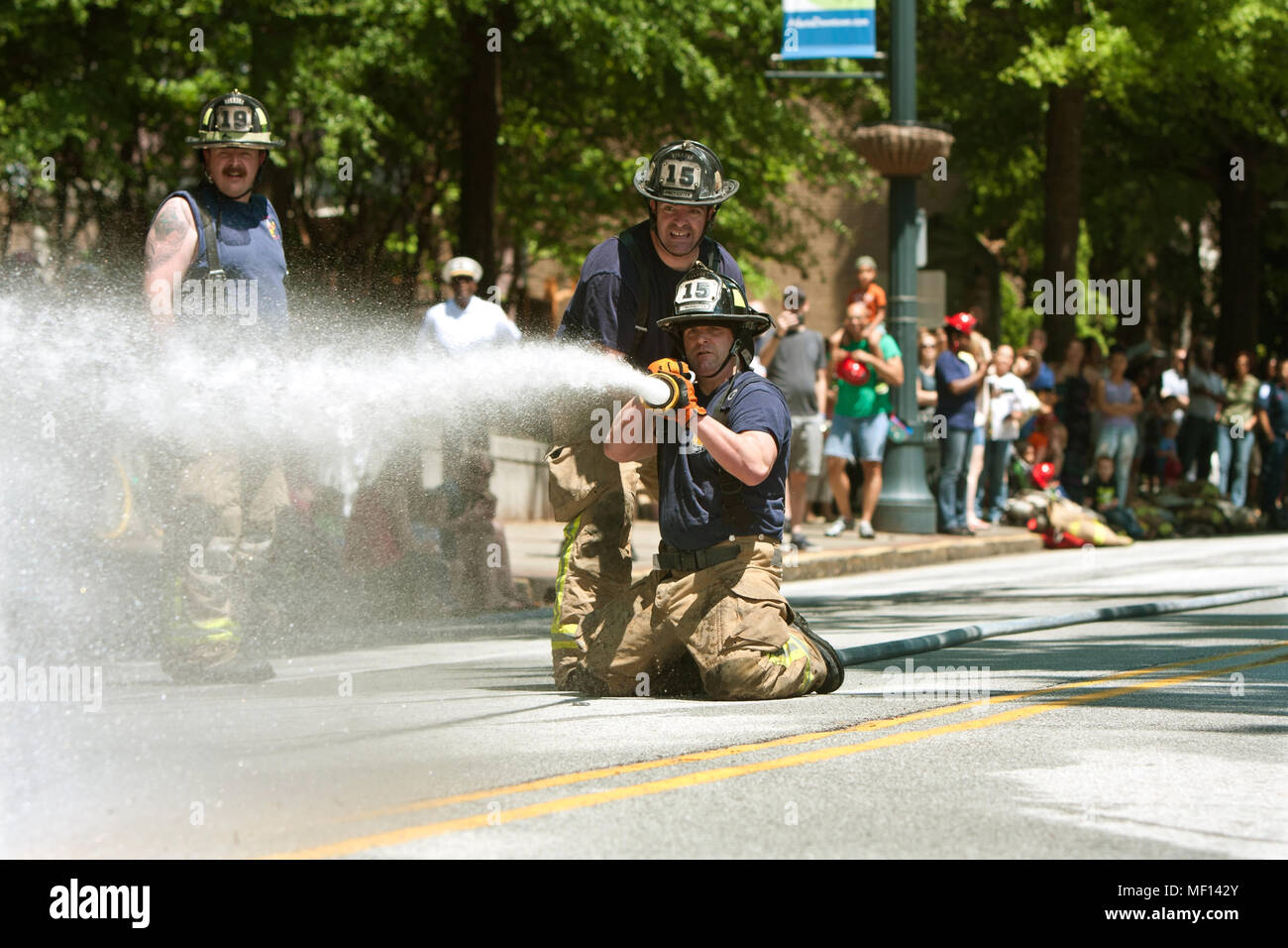 Firemen aim a fire hose at a target in a fireman muster competition between local fire departments, on May 2, 2015 in Atlanta, GA. - Stock Image