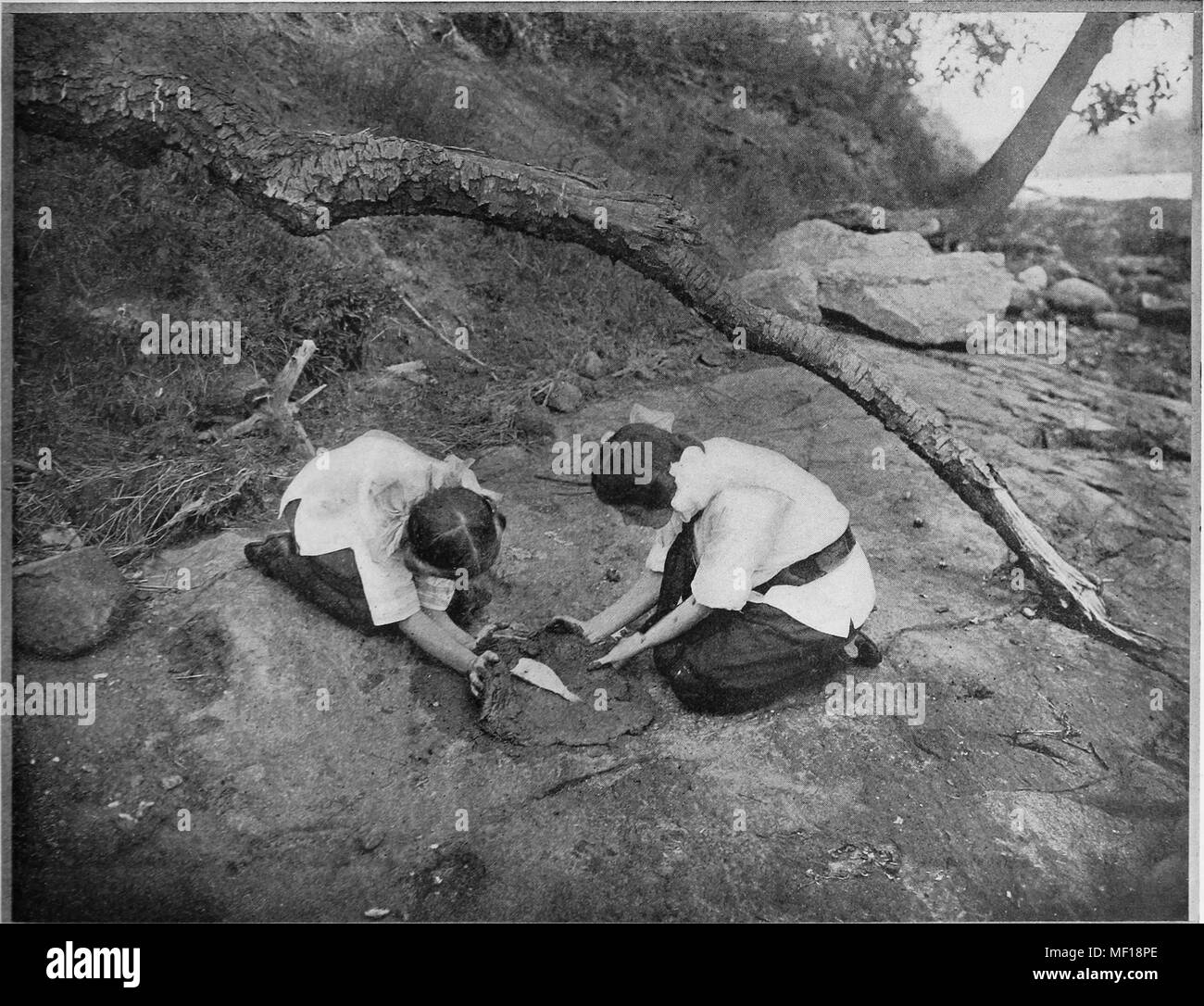 Black and white photograph of two women outdoors, preparing a fish for baking by rubbing soft clay on it, 1905. Courtesy Internet Archive. () - Stock Image