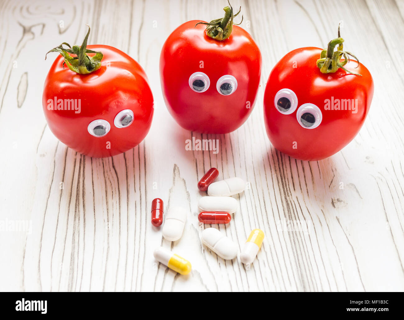 Tomatoes with wobbly eyes looking at vitamin supplements - Stock Image