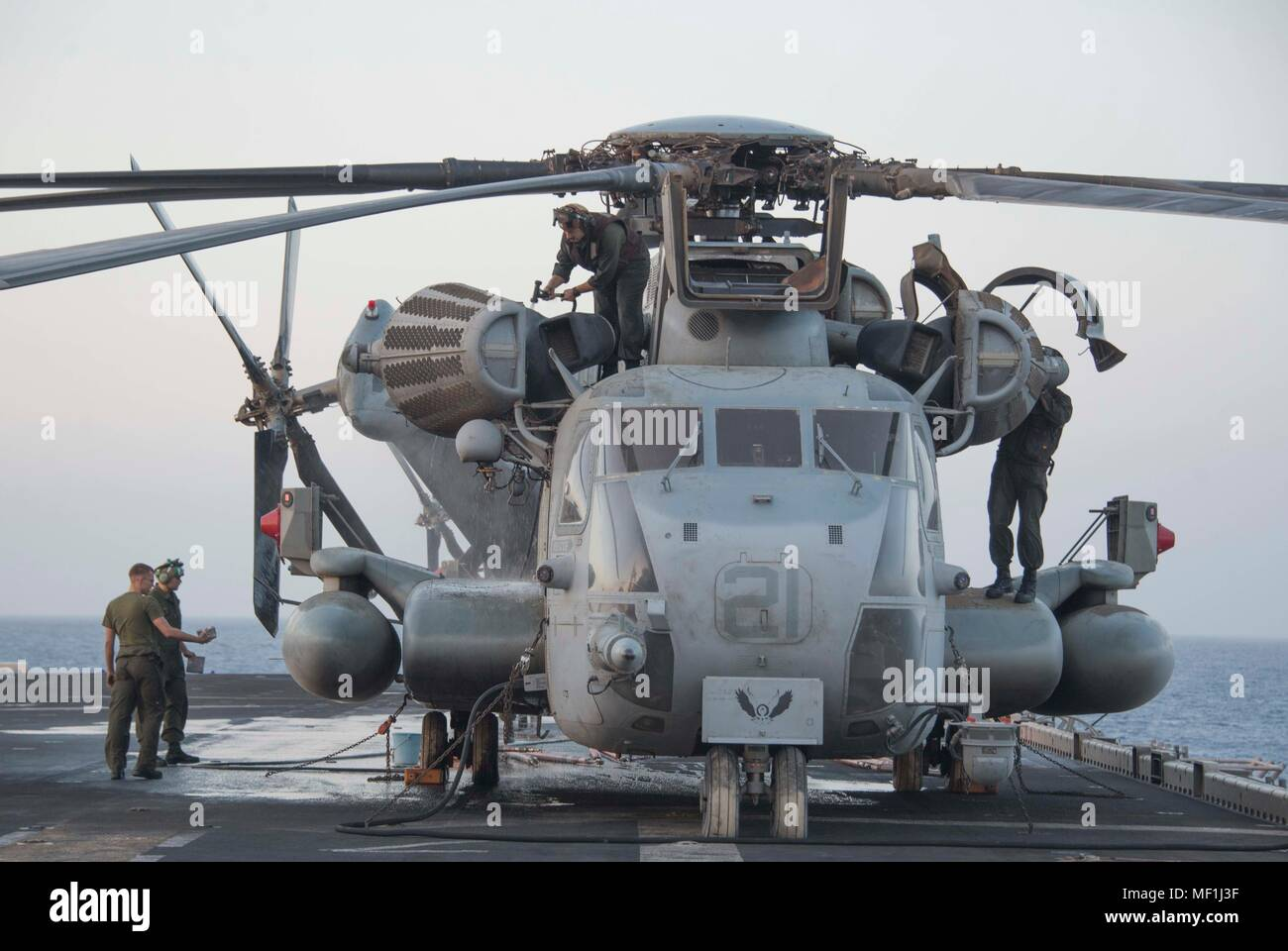 U.S. 5TH FLEET AREA OF OPERATIONS (April 19, 2018) Marines wash down a CH-53E Super Stallion, attached to Marine Medium Tiltrotor Squadron (VMM) 162 (Reinforced), on the flight deck of  the Wasp-class amphibious assault ship USS Iwo Jima (LHD 7) April 19, 2018. Iwo Jima, homeported in Mayport, Fla., is on a regularly scheduled deployment to the U.S. 5th Fleet area of operations in support of maritime security operations to reassure allies and partners, and preserve the freedom of navigation and the free flow of commerce in the region. (U.S. Navy photo by Mass Communication Specialist Seaman Da Stock Photo