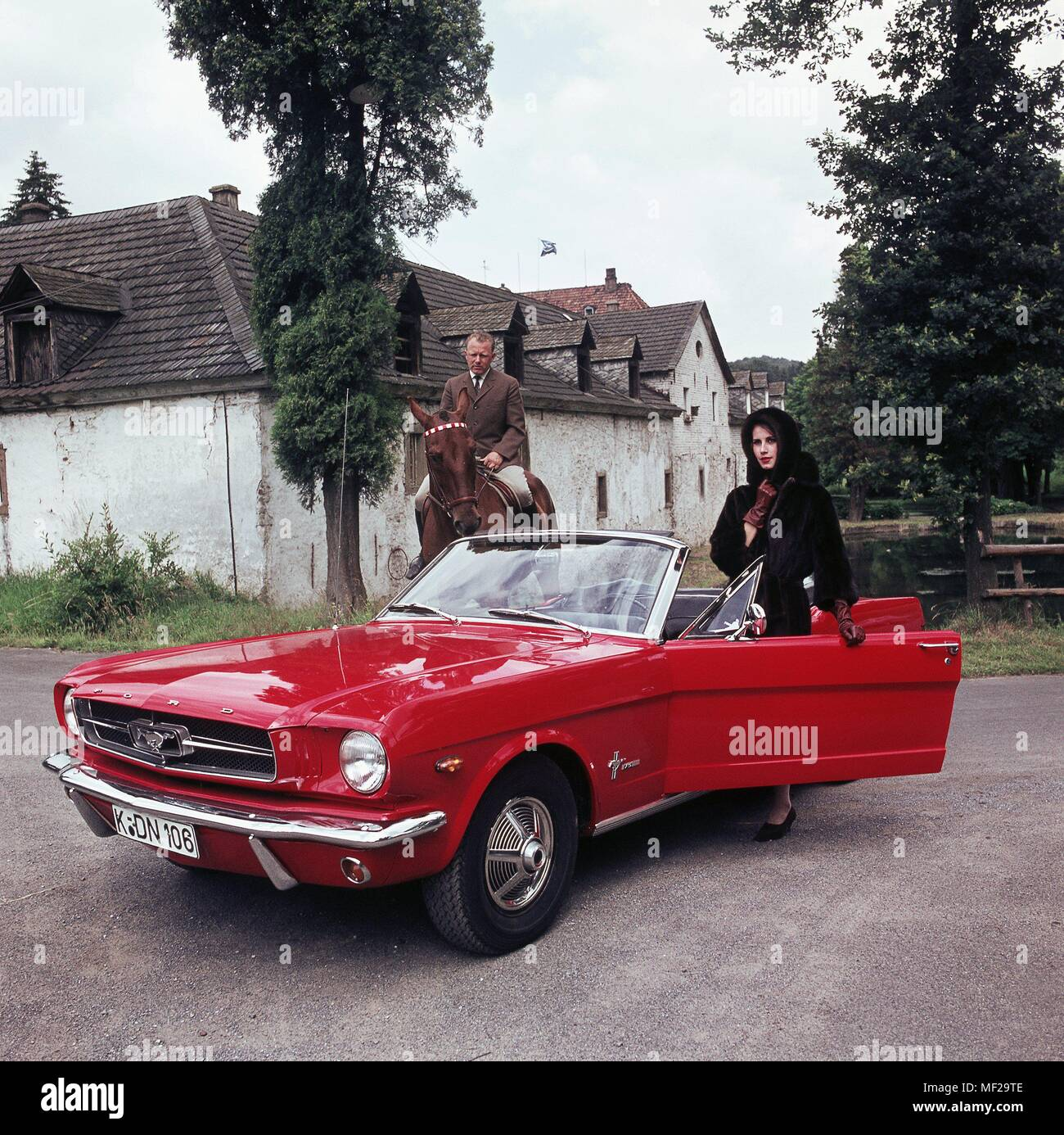 A rider on horseback next to a red ford mustang cabriolet shot in the 70s usage worldwide