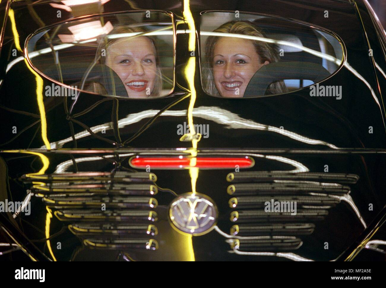 Tatjana (l) and Turkan (r) look at the International Motor Show (IAA) on 15.9.1999 through a so-called 'pretzel window' of a new VW Beetle. The VW Kafer of the first series also had the two-part rear window, which is now installed by the car accessories company Abt in the new Beetle. Just under a year after the introduction of the New Beetle in Germany, Volkswagen is responding to the weak sales figures with a cheaper model. Offered is now a New Beetle for the base price of 30450 DM (15570 Euro). That is about DM 5,000 less than the most favorable model of the Kafer successor to date. The engi - Stock Image
