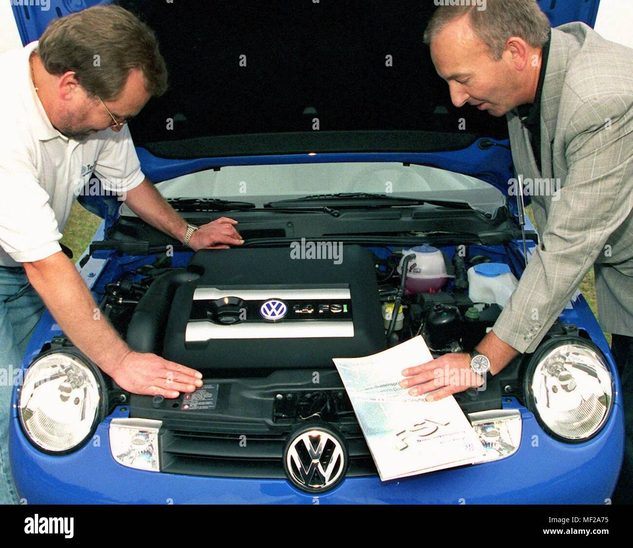 A gasoline-saving direct-injection engine, the Volkswagen offers as the first European automaker in a VW Lupo from withte 2000, consider on 10.9.1999 at the presentation of the 1.4-liter engine in Lower Saxony Jeversen the factory employees Gerhard Spitzer (l) and Klaus Badtke (r). The engine should this week one of the technical highlights of the International Motor Show (IAA) in Frankfurt/Main. Due to the new technology, Lupo consumption and exhaust gases are dropping in the small car. Full advantage of the direct injection but only with sulfur-free fuel. VW therefore urges its short-term - Stock Image