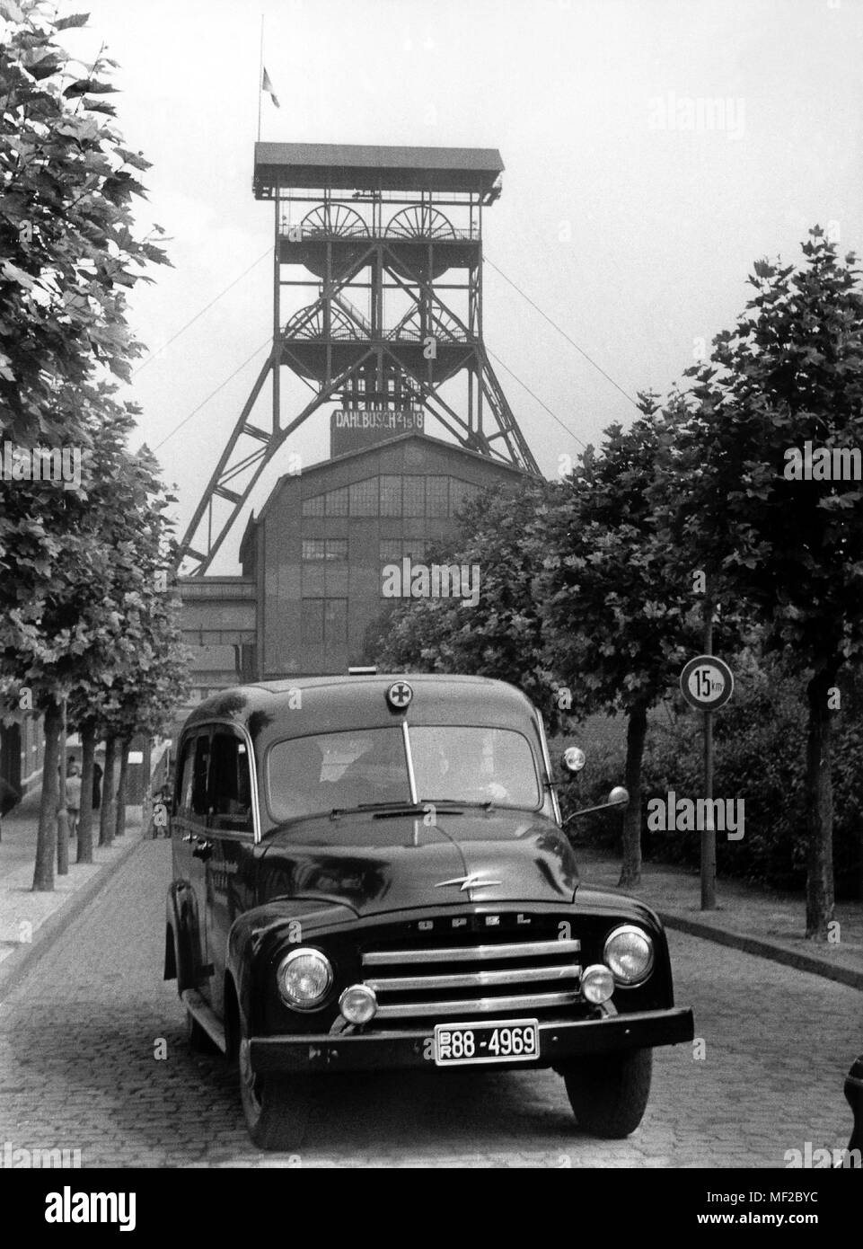 A sanitary car leaves the colliery. In the background, the demand tower of Schacht Dahlbusch 2/5/8 with a flag waving at half mast. On August 3, 1955 occurred at the colliery Dahlbusch in Gelsenkirchen between the tenth and eleventh sole on shaft 8 a crash explosion in which a total of 41 miners were killed and 21 were seriously injured. Twenty-five buddies who were close to the blast furnace could not be rescued due to the strong mine fire in the affected Strebs. After the rescue work was stopped, these corridors were walled up to prevent the fire from spreading. As early as May 1955, three m - Stock Image