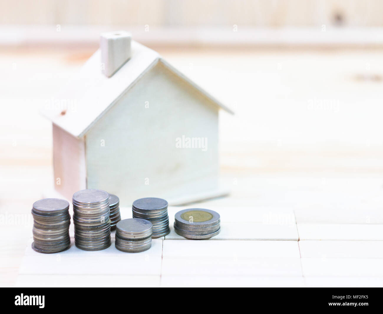 coins and house is located on a wooden floor - Stock Image