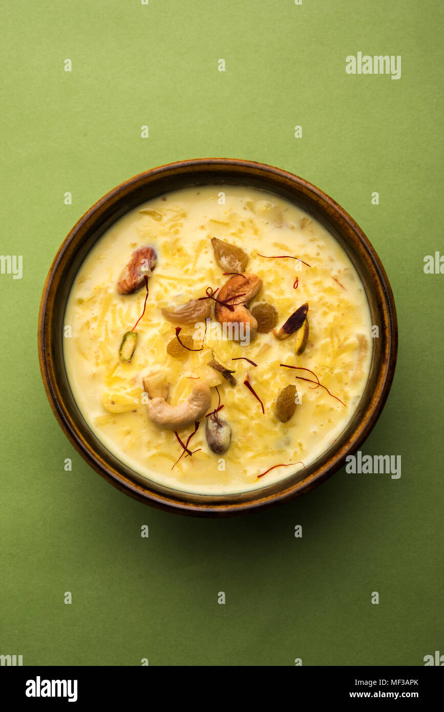kheer or rice pudding is an Indian dessert in a brown terracotta bowl with dry fruits toppings - Stock Image