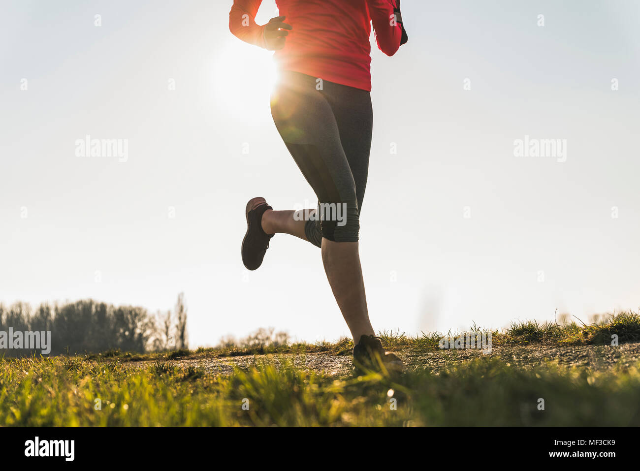 Low section of woman running on rural path - Stock Image
