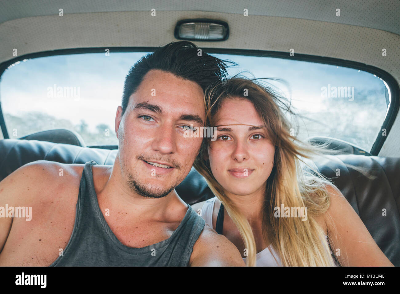 Cuba, Yound couple sitting in a vintage car, taking a selfie Stock Photo