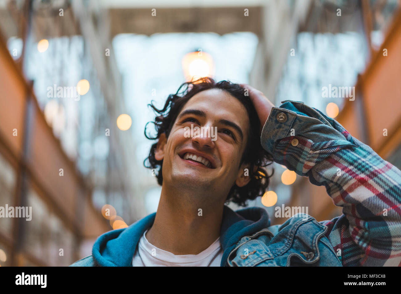 Portrait of smiling young man in shopping centre - Stock Image