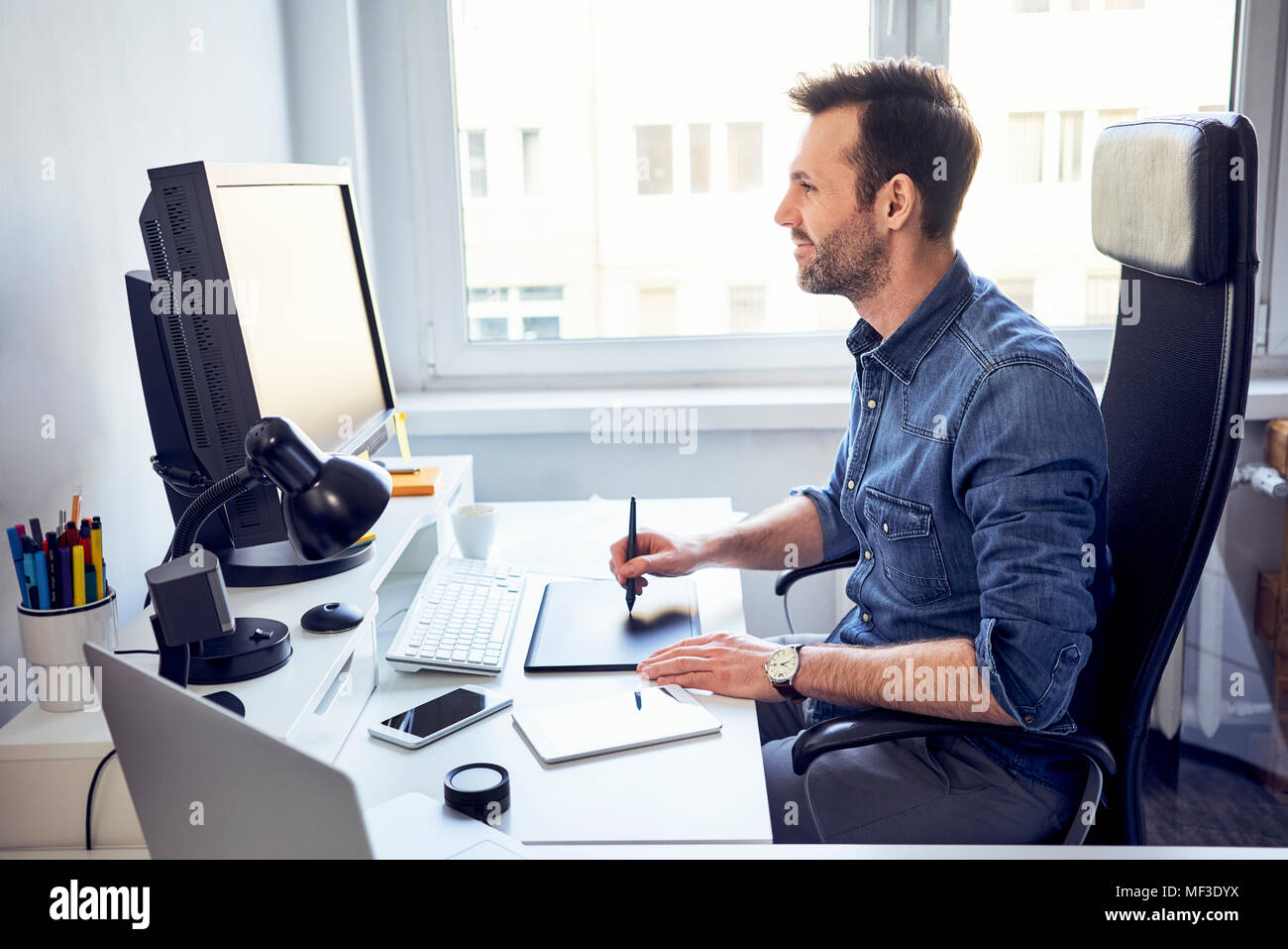 Smiling graphic designer working on computer at desk in office - Stock Image