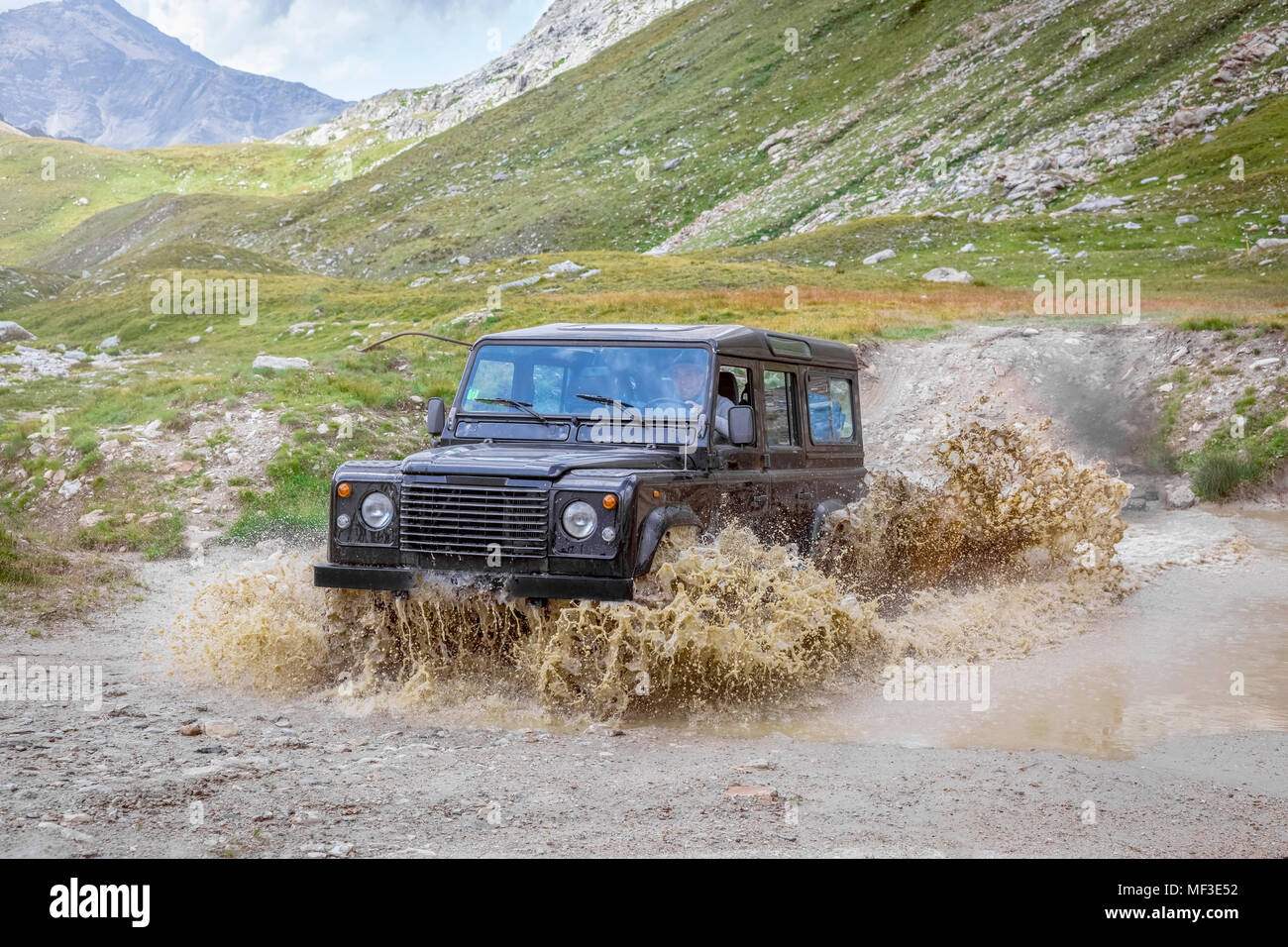 Italy, Piemont, Landrover driving through waterhole - Stock Image