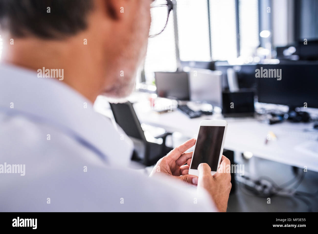 Close-upof businessman in office using smartphone - Stock Image