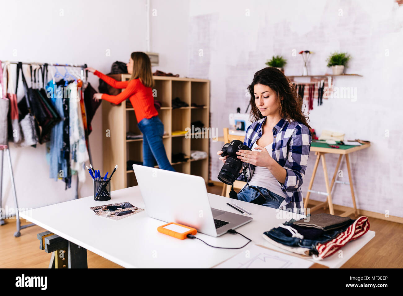 Fashion designer with camera and laptop in studio - Stock Image