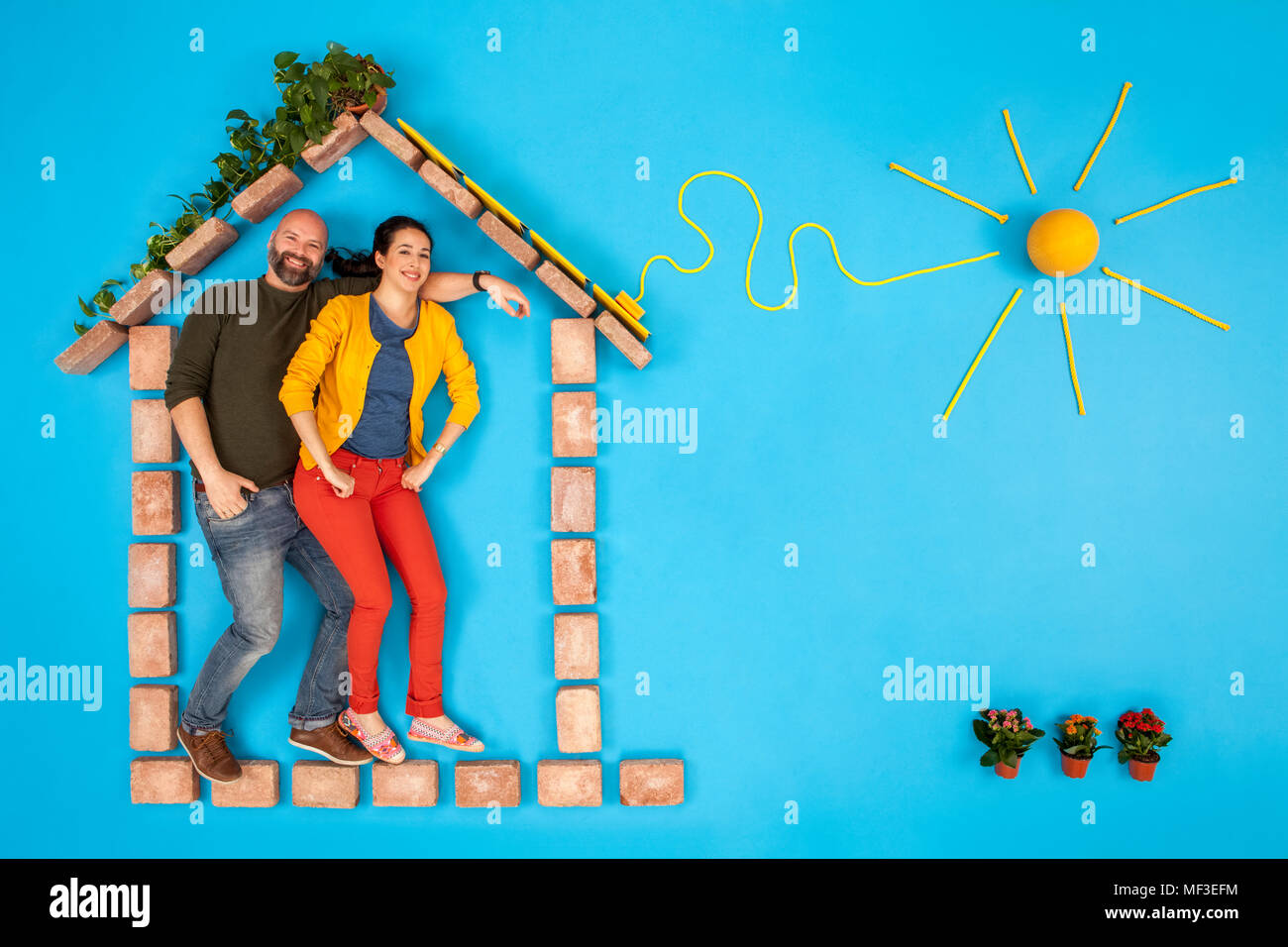 Happy couple standing in house, with solar panels plugged to sun - Stock Image