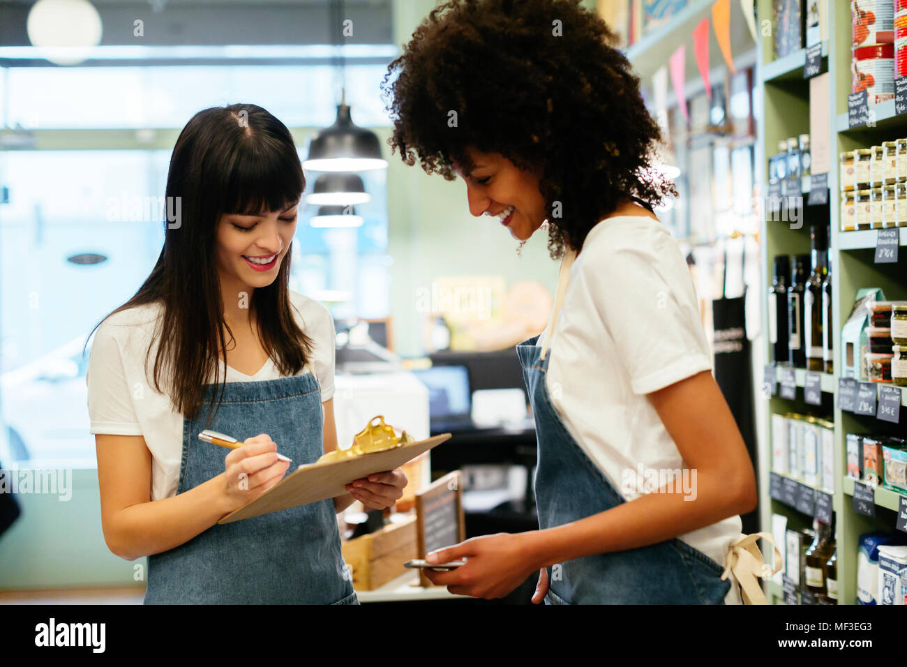 Two smiling women in a store with clipboard - Stock Image