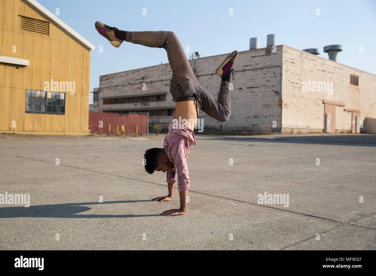Young man doing a handstand outdoors - Stock Image