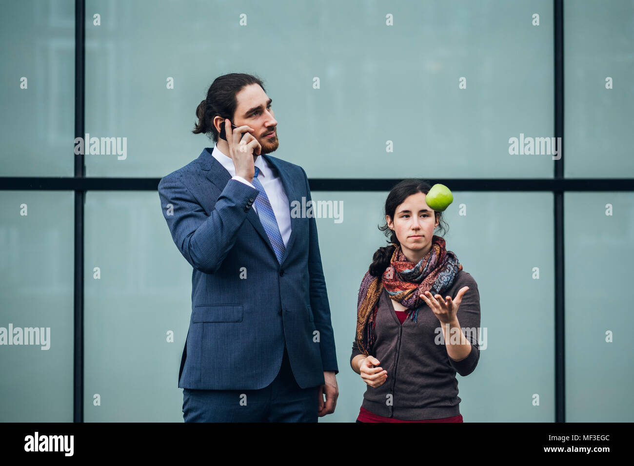Businessman talking on cell phone and woman throwing an apple - Stock Image