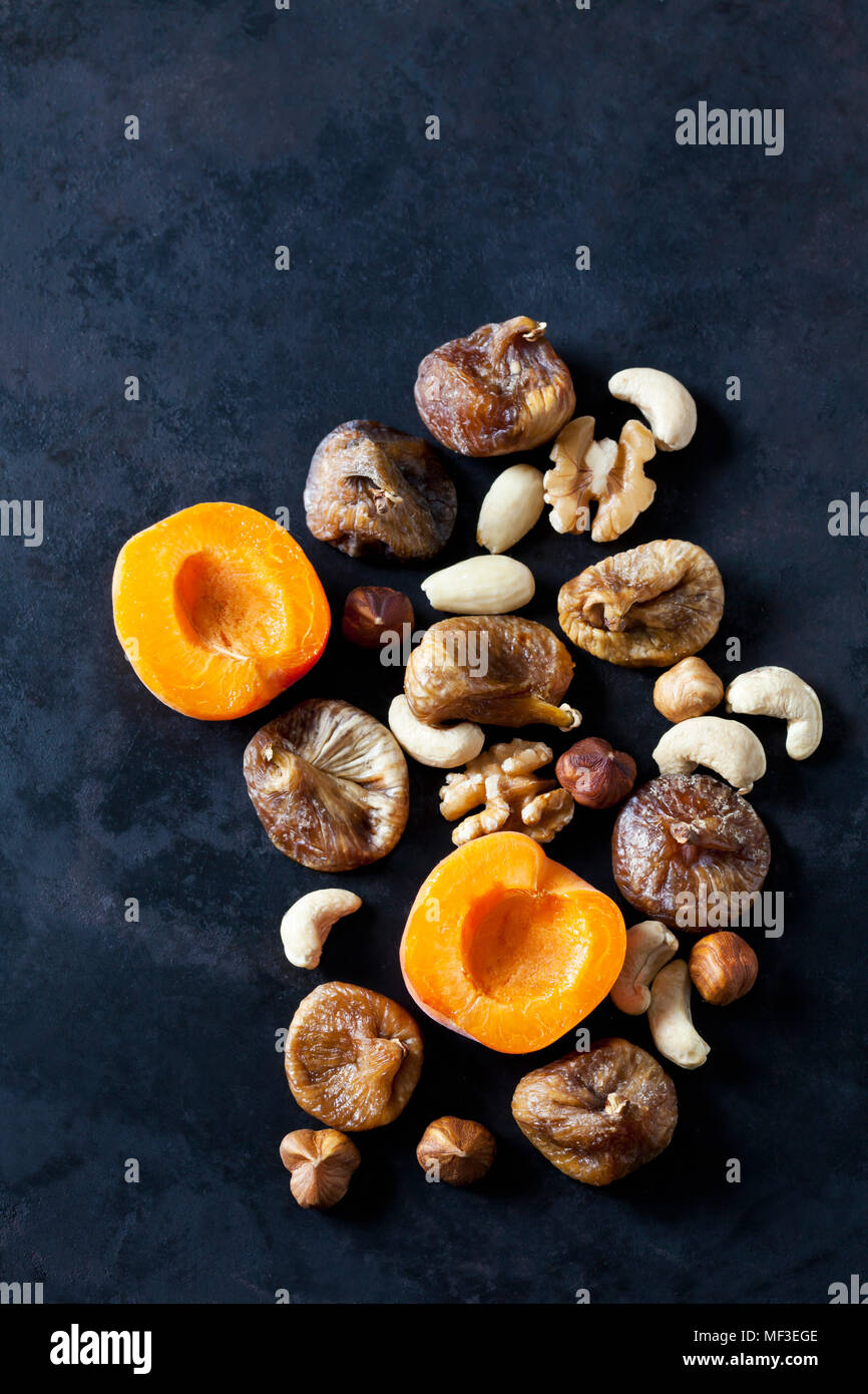 Sliced apricot, dried figs, almonds and various nuts on dark ground - Stock Image