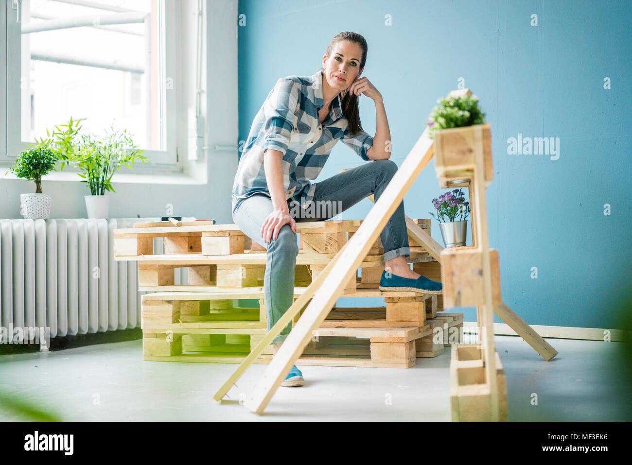 Beautiful woman refurbishing her home with pallets - Stock Image